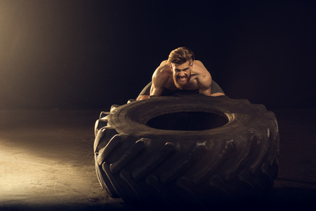Photo pour muscular sportsman training with big tire on black with side lighting - image libre de droit