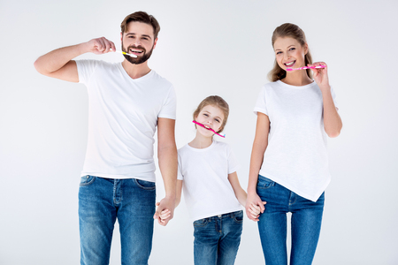 Photo for Happy family in white t-shirts cleaning teeth with toothbrushes - Royalty Free Image