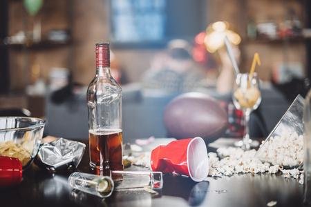 Foto de Close-up view of popcorn, glasses and trash on messy table after party - Imagen libre de derechos