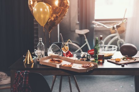 Photo pour Messy table with pizza in box and beverages at morning - image libre de droit