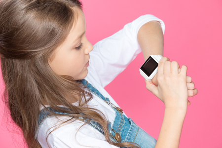 Foto per cute little girl using smartwatch on pink - Immagine Royalty Free