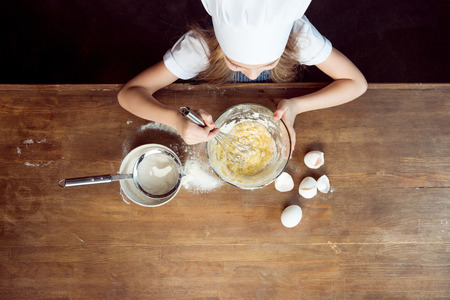 girl making dough for cookies on wooden table