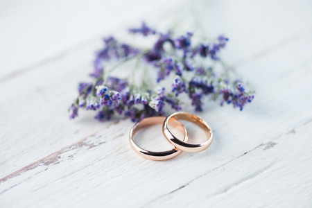 Photo pour golden wedding rings and beautiful small blue flowers on wooden tabletop - image libre de droit