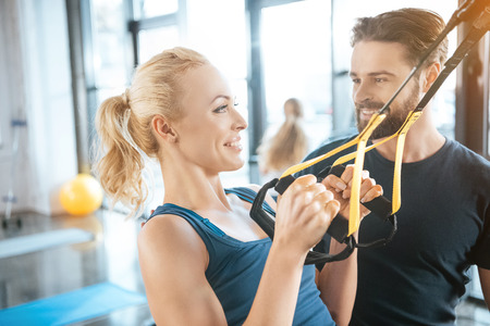 Photo for Coach talking with blonde fitness woman training with trx fitness straps - Royalty Free Image