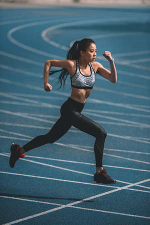 Photo pour sportswoman training on running track stadium, young girl running concept - image libre de droit