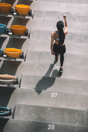 Photo pour elevated view of sportswoman running on stadium stairs - image libre de droit