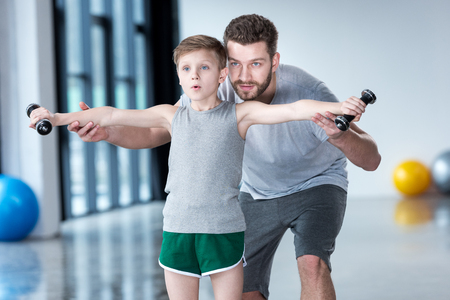 Foto de Boy training with dumbbells together with coach - Imagen libre de derechos