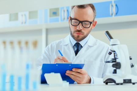 Foto de young doctor in uniform working at testing laboratory at clinic - Imagen libre de derechos