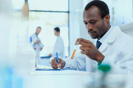 Foto de African american scientist in white coat holding and examining test tube with reagent - Imagen libre de derechos