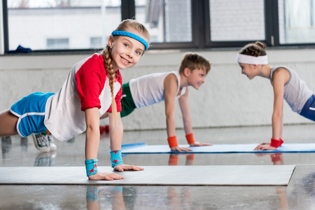 Photo for Cute sporty kids exercising on yoga mats in gym and smiling - Royalty Free Image