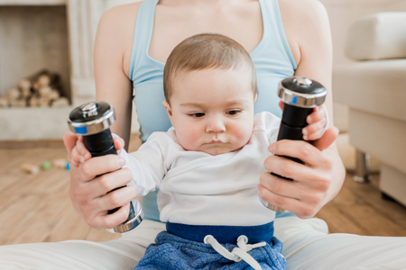 Photo for woman and baby boy playing with dumbbells at home - Royalty Free Image
