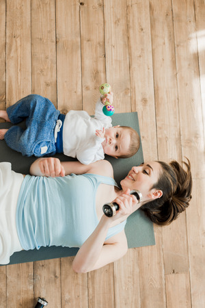 Photo pour mother with baby boy lying on floor and playing with dumbbells - image libre de droit