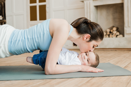 Photo for woman doing plank exercise and kissing her son - Royalty Free Image
