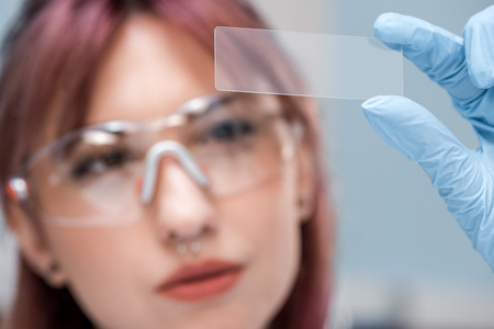 Photo for concentrated young scientist in eyeglasses holding glass microscope slide in chemical laboratory - Royalty Free Image