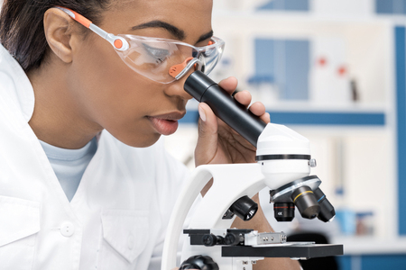 Foto de african american scientist in lab coat working with microscope in chemical lab - Imagen libre de derechos