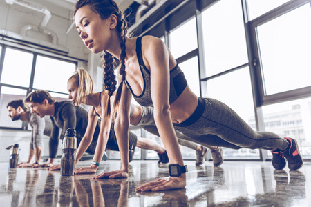 Foto per group of athletic young people in sportswear doing push ups or plank at the gym - Immagine Royalty Free