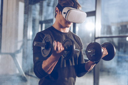 Photo pour man in virtual reality headset exercising with dumbbells in gym - image libre de droit