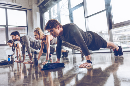 Photo pour group of athletic young people in sportswear doing push ups or plank at the gym - image libre de droit