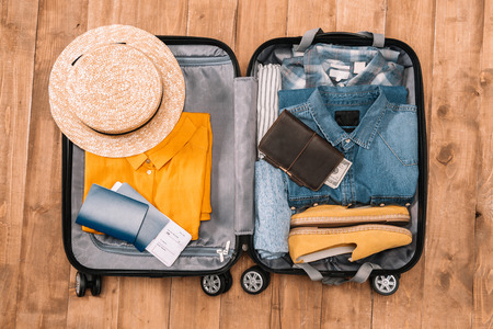 Photo pour Ready for travel concept. Top view of essentials for tourist with clothes, accessories and gadgets, wallet, passport, smartphone in bag. - image libre de droit