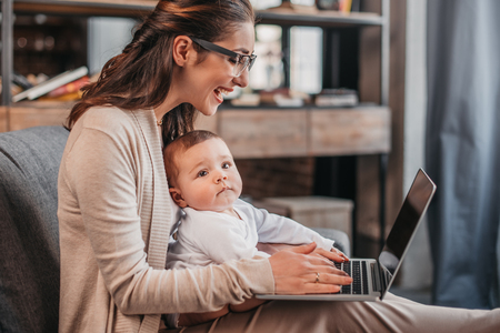 Photo pour happy mother with her son using laptop at home - image libre de droit
