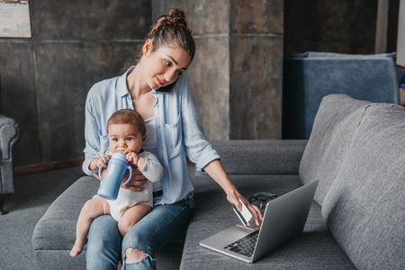 Foto de mother with baby boy remote working and using laptop during conversation on smartphone - Imagen libre de derechos