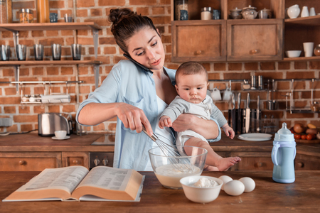Foto de mother holding her son, talking on smartphone and mixing a dough at the kitchen. family life and multitasking concept - Imagen libre de derechos