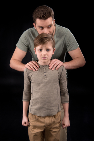 Foto de Father putting hands on shoulders of scared little son - Imagen libre de derechos