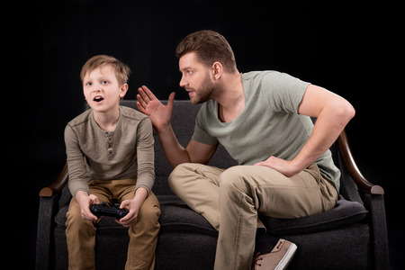 Foto de Father trying to talk with little son playing with joystick - Imagen libre de derechos