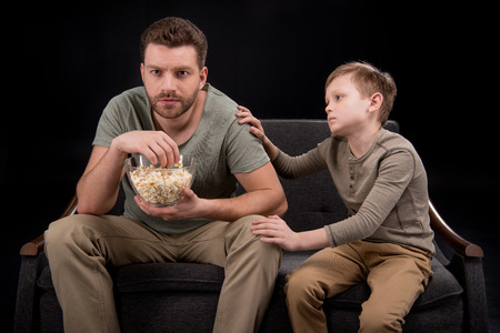 Foto de Little boy trying to talk with father eating popcorn and watching tv on sofa - Imagen libre de derechos