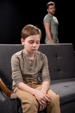 Foto de Upset little boy sitting on sofa and father standing behind - Imagen libre de derechos