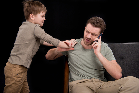 Foto de Upset little boy trying to talk with father talking on smartphone - Imagen libre de derechos
