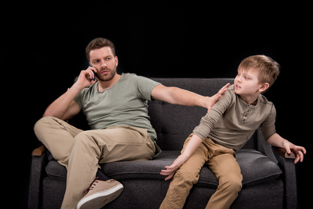Foto de Bearded man talking on smartphone and pushing little son sitting on sofa - Imagen libre de derechos