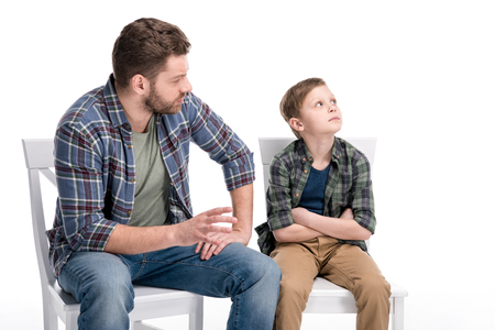 Foto de Father talking with little son sitting on chair with crossed arms and looking up - Imagen libre de derechos