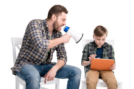 Photo for Father with megaphone screaming at son using digital tablet - Royalty Free Image