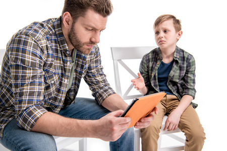 Foto de Upset little boy trying to talk with father using digital tablet - Imagen libre de derechos