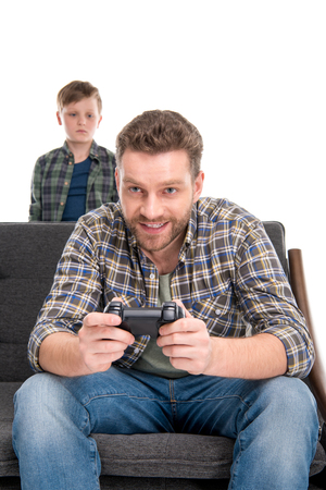 Foto de Little boy looking at father sitting on sofa and playing with joystick - Imagen libre de derechos