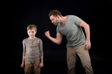 Foto de Angry father threatening and gesturing to scared little son, - Imagen libre de derechos