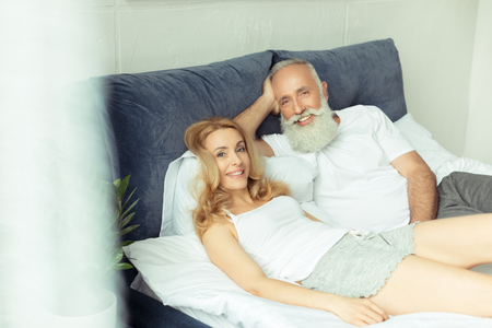 Foto de mature couple relaxing on bed and looking at camera at home - Imagen libre de derechos