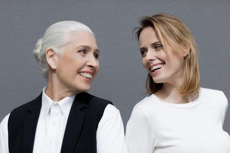 Foto de Two beautiful women standing together and smiling each other - Imagen libre de derechos