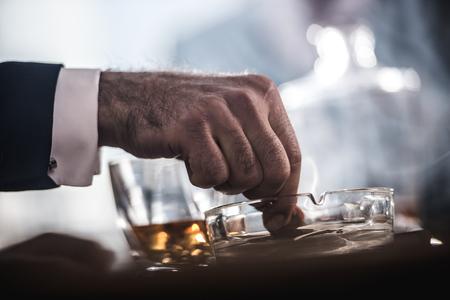 Foto de businessman extinguishing cigar in glass ashtray - Imagen libre de derechos