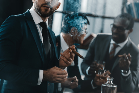 Photo pour businessman smoking cigar with multicultural business team - image libre de droit