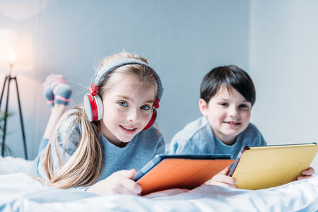 Foto de girl in headphones and little boy using digital tablets while lying - Imagen libre de derechos