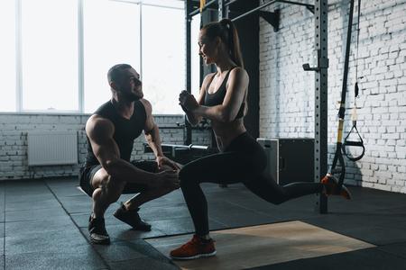 Foto de sportswoman squatting with trx resistance band while trainer helping her - Imagen libre de derechos