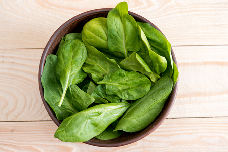 Photo for green spinach leaves in ceramic bowl on wooden tabletop - Royalty Free Image
