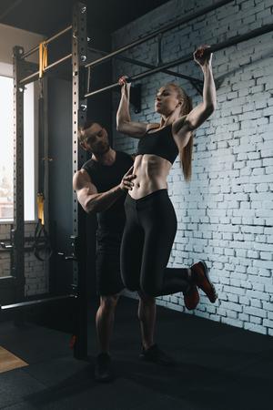 Foto de sportswoman doing pull up while trainer helping her - Imagen libre de derechos