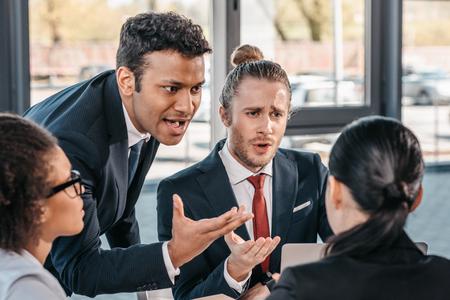 Foto de young emotional businesspeople in formalwear arguing at meeting in office, business team meeting - Imagen libre de derechos
