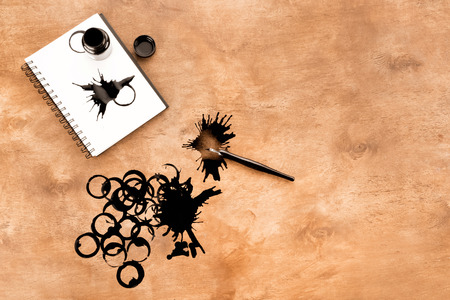 Foto de ink container, fountain pen, notebook and ink splashes on table - Imagen libre de derechos