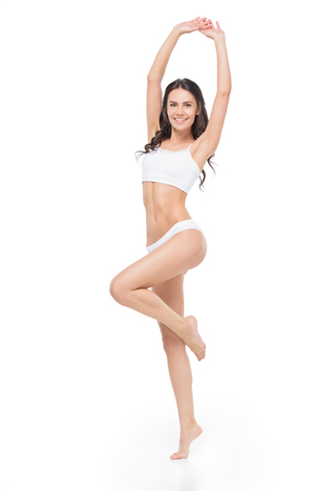 Photo pour Smiling young woman in underwear posing with raised hands - image libre de droit