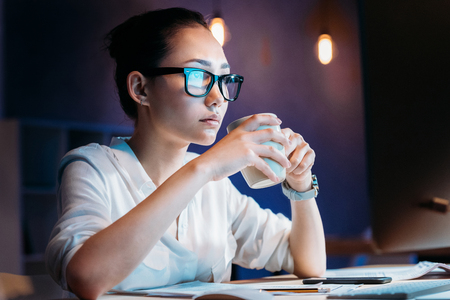 Foto de businesswoman in eyeglasses holding cup while working late in office - Imagen libre de derechos