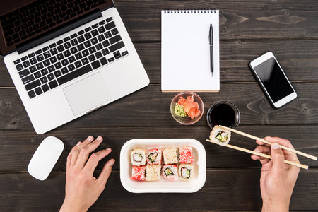 Photo for Top view of laptop with computer mouse, blank notebook with pen, smartphone and sushi set - Royalty Free Image